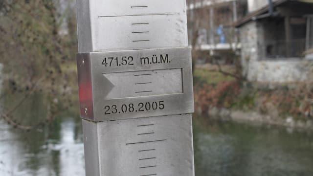 Hochwassertafel mit Fluss im Hintergrund.