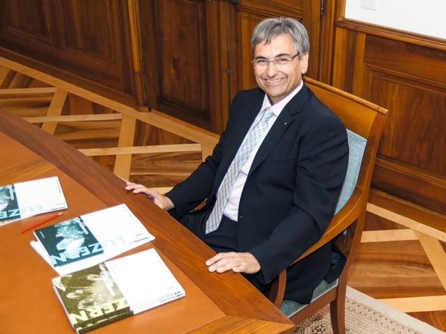 Guido Graf sitzt an einem Tisch mit der Staatsrechnung auf der Tisch.