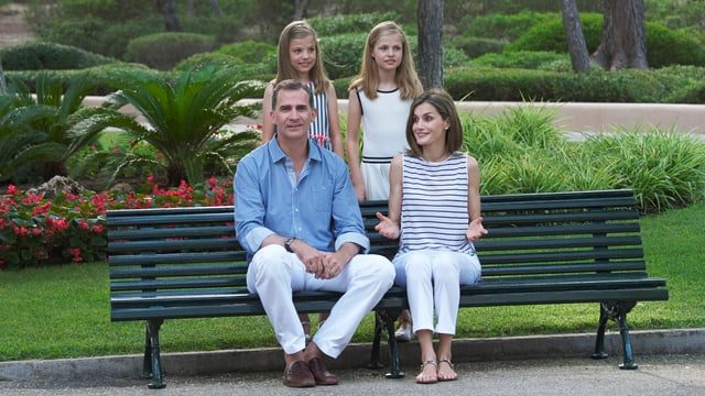 Das Königspaar sitzt auf einem Bank, dahinter stehen die Töchter.