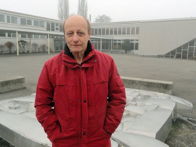 Ein Mann vor einem Schulhaus-Areal.