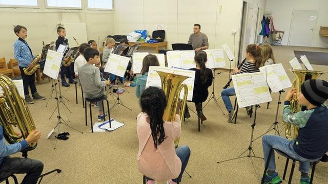 Eine Schulklasse spielt auf verschiedenen Musikinstrumenten.