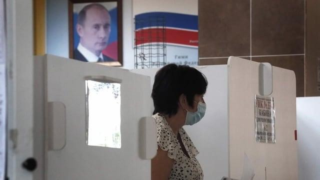 Frau mit Mundschutz – im Hintergrund ist Plakat mit Wladimir Putin zu sehen.