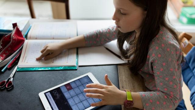 Mädchen macht Hausaufgaben und tippt auf Tablet rum