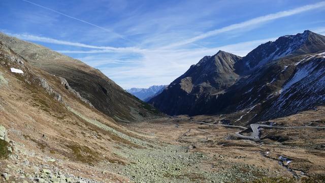 Ein breites Tal mit einer Passtrasse am rechten Bildrand. Links erhebt sich ein mässig steiler Hang mit viel Geröll.