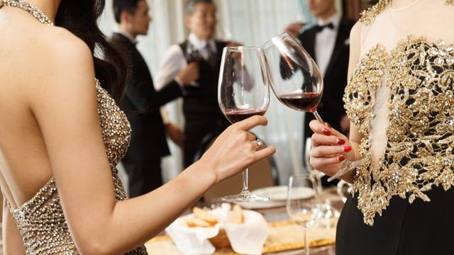 Zwei Frauen im Abendkleid stossen an einem Fest mit Rotwein an.
