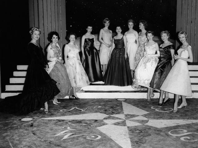 Elf Frauen in langen Roben posieren auf einer Treppe.