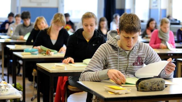 Maturanden sitzen einzeln an Tischen und lösen eine Prüfung.