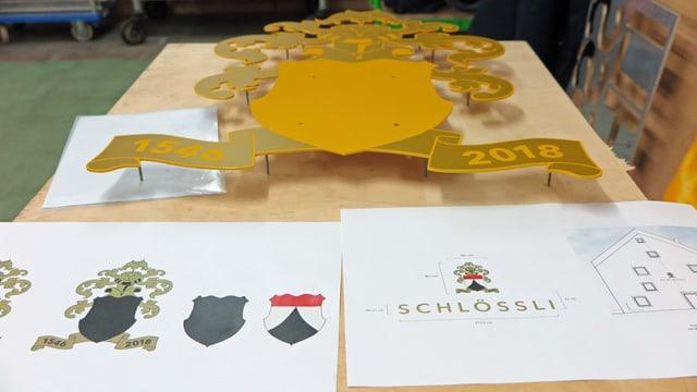 Metallwappen für Schlössli Wohlen auf einem Tisch, davor Planzeichnung für Installation des Wappens