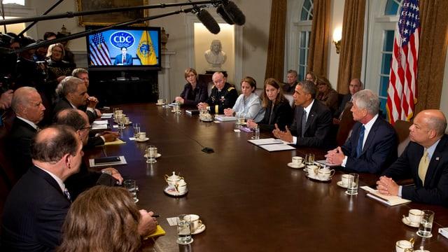 Obama sitzt an einem langen Tisch mit vielen Mitarbeitern, hinten ein TV-Bildschirm.