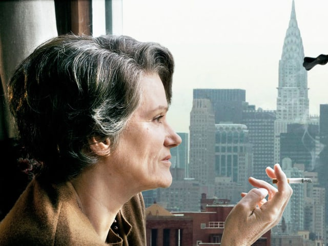 Hannah Arendt sitzt am Fenster und raucht eine Zigarette.
