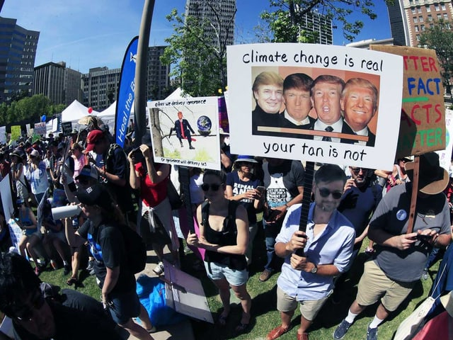 Ein Mann hält ein Plakat, auf dem Trump mit vier verschiedenen Hautfarben abgebildet ist.