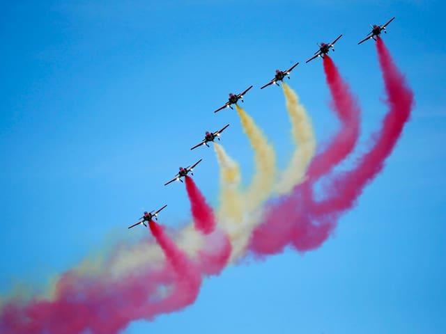 Blauer Himmel mit 7 Jets der Spanischen Kunstflugstaffel. Sie haben farbigen Rauch: Ein Streifen rot, dann weiss, dann wieder rot.