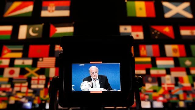 Eine Kamera zeigt Sepp Blatter und im Hintergrund hat es viele Länderfahnen
