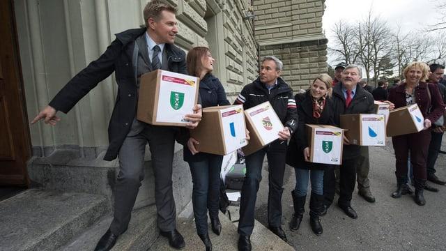 SVP-Präsident Toni Brunner und weitere Aktivisten reichen sich Schachteln mit Unterschriften weiter.