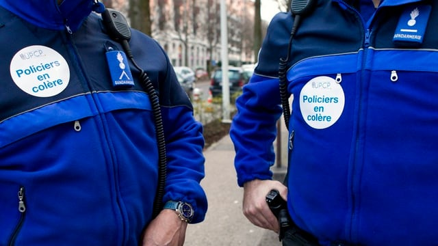 Purtret da dus policists cun si il logo da la UPCP.