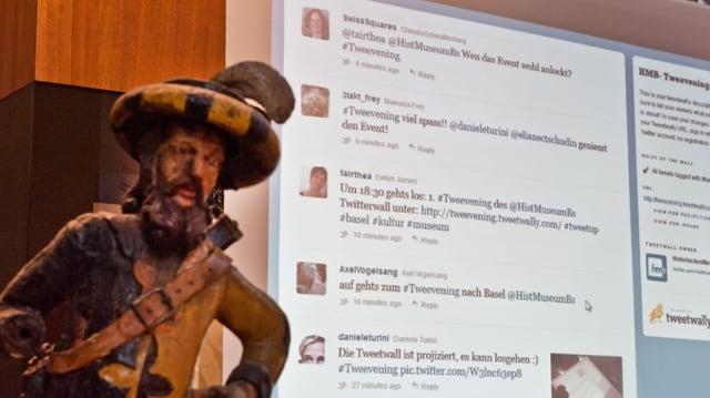 Leinwand mit Twitter-Nachrichten, davor eine Statue.