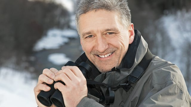Andreas Moser hält ein Fernglas und freut sich.