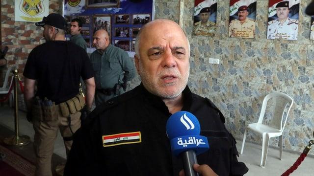 Al-Abadi en ina chasa, discurrind en il microfon.