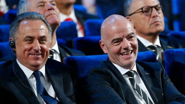 Witali Mutko und Gianni Infantino sitzen lachend nebeneinander.