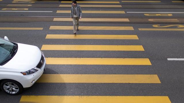Ein Auto fährt über einen Fussgängerstreifen, und ein Fussgänger überquert die Strasse.