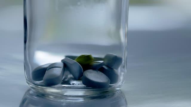 Ein Glas mit Pillen darin