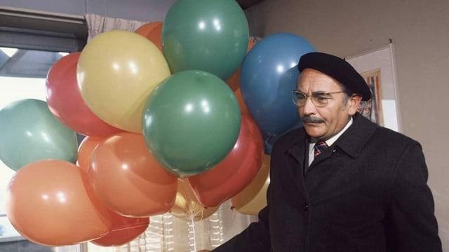 Ruedi Walter mit vielen farbigen Ballons in einem Raum.