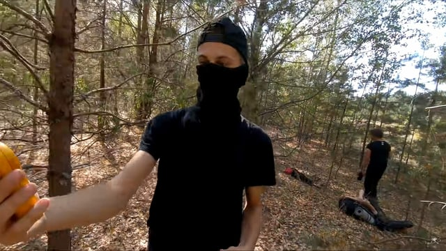 Ein junger Mann mit verhülltem Gesicht in einem Wald, er schaut auf ein gelbes Gerät.