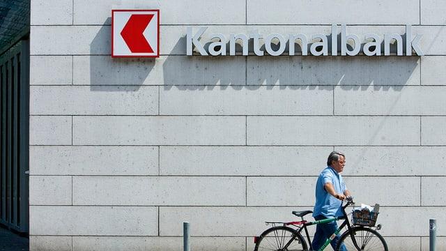 Vor dem Logo der Kantonalbank Basel-Landschaft schiebt ein Mann ein Velo.