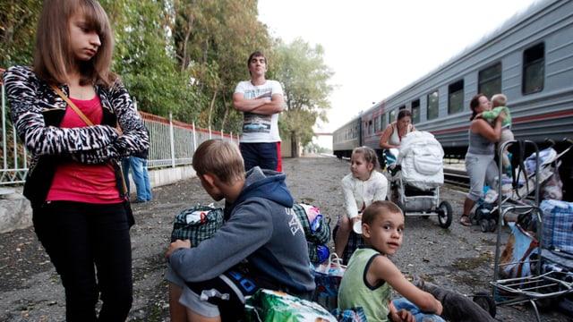 Mütter mit Kindern und einige Jugendliche stehen und sitzen neben einem Zugswaggon.
