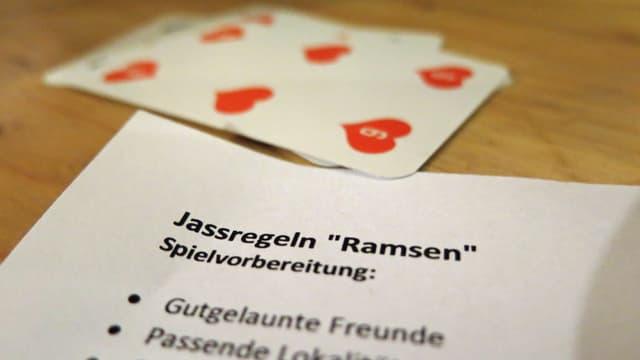 Jasskarten und ein Regelblatt auf einem Tisch.