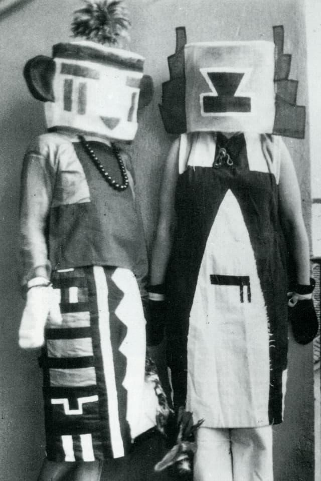 Zwei Figuren in Kostümen mit geometrischen Mustern, komplett verkleidete mit Maske.