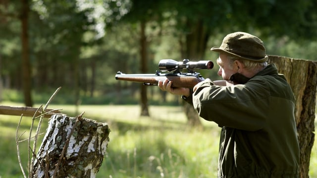Jäger zielt mit Gewehr und Zielfernrohr