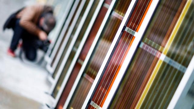 Rot-gelbe Fotozellen an einer Hausfassade, im Hintergrund kniet ein Mann, der nur unscharf zu sehen ist.