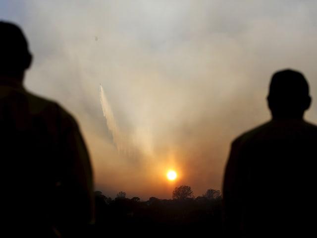 Feuerwehrmänner beobachten, wie ein Lösch-Helikopter am Horizont Wasser auf einen Brandherd schüttet.