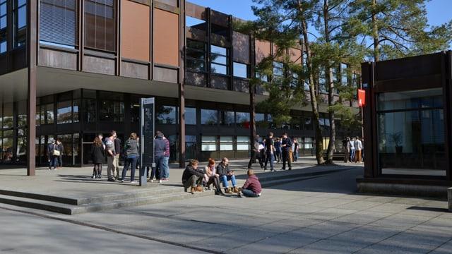 Schulgebäude mit Studierenden.