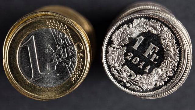 Ein Einfränkler liegt neben einem Ein-Euro-Stück.