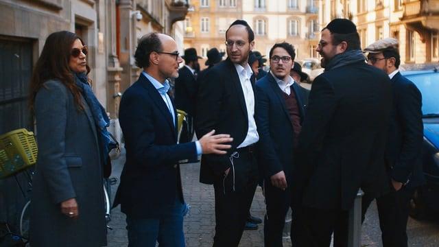Ein Mann und eine Frau sprechen mit einer Gruppe jüdischer Männer mit Kippa.