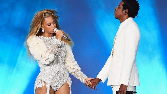 ein Paar in weiss gekleidet hält Händchen und singt ins Mikrofon