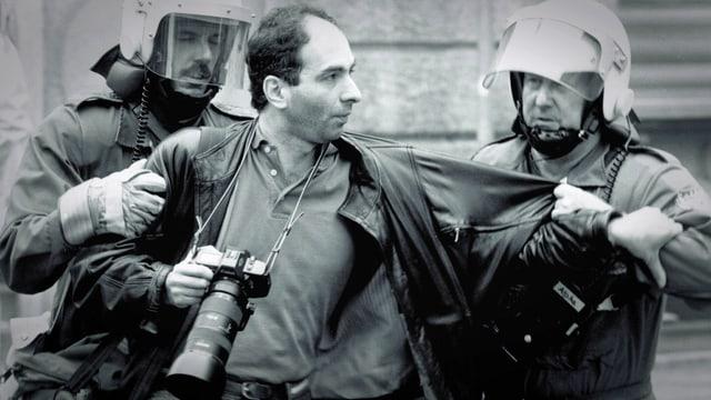 Schwarzweissfoto: Fotograf Klaus Rosza wird von zwei Polizisten bei der Arbeit behindert.