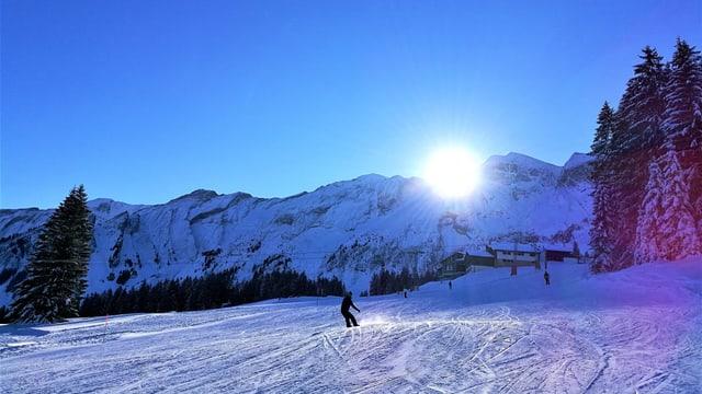 Skifahrer carvt in Sörenberg der Sonne entgegen.