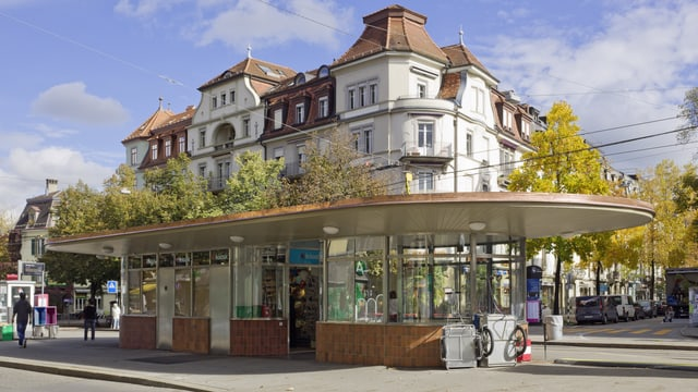 Das Tramwartehäuschen, ein Pavillon aus Glas und Holz mit Flachdach.