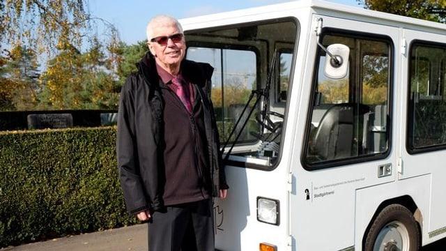 Marc Lüthi, Leiter des Bestattungswesens in Basel, neben dem Friedhof-Elektrobus.