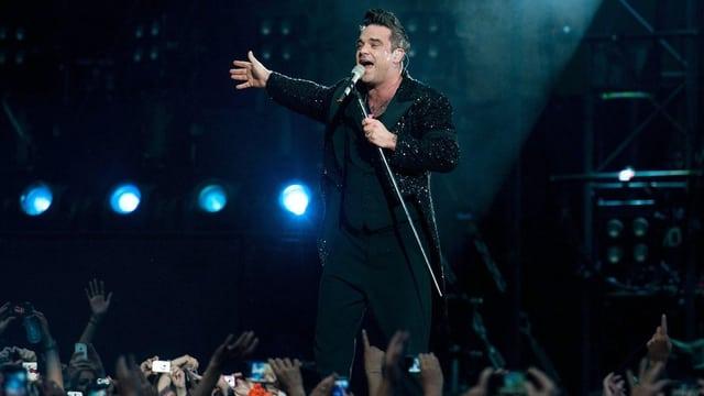 Robbie Williams singt ins Mikrofon, im Vordergrund die in die Höhe gestreckten Arme des Publikums
