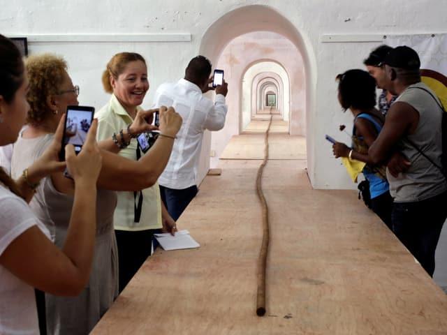 Menschen fotografieren die längste Zigarre der Welt.
