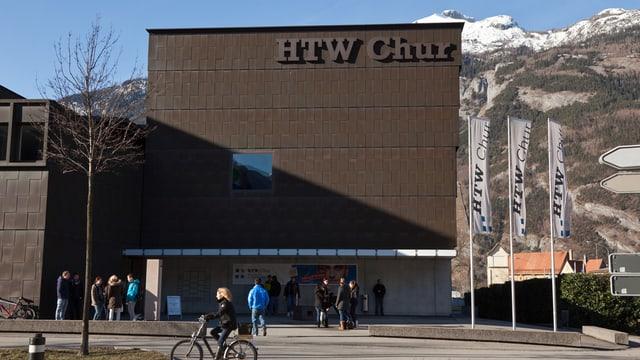 Die Fassade der HTW Chur. Davor sind Passanten und eine Velofahrerin zu sehen.