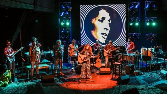 Eine Frau auf einer Bühne, im Hintergrund ein Bild von Joan Baez.