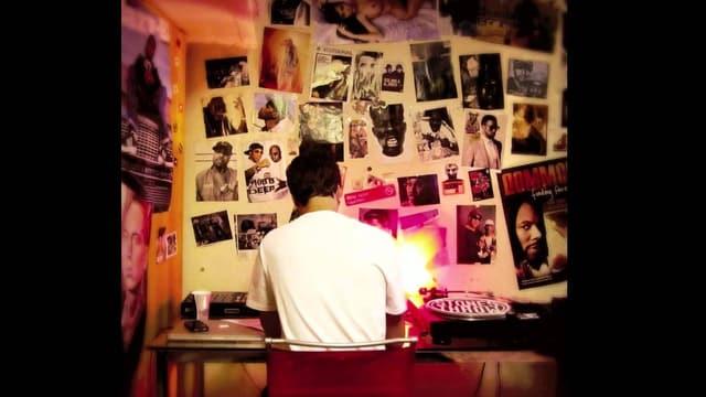 Ein Mann sitzt mit dem Rücken zur Kamera an einem Tisch vor einer Posterwand