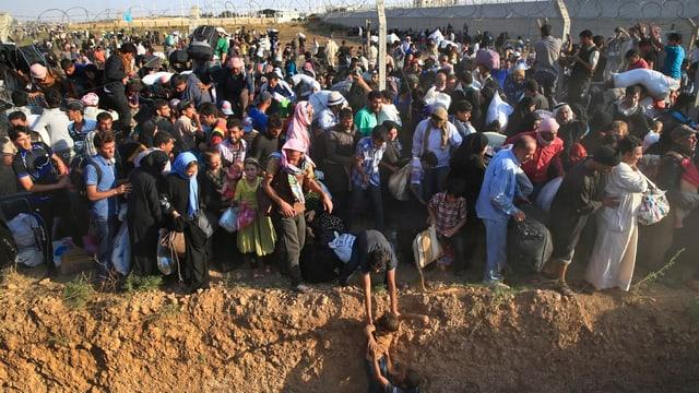 Syrische Flüchtlinge betreten türkischen Boden.
