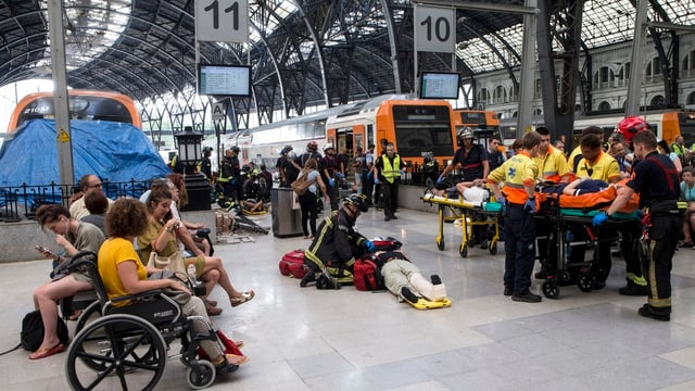 Persunas salvadas e medis en la staziun da Barcelona.