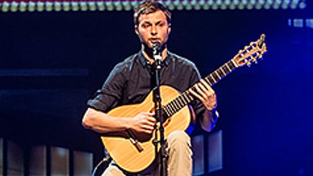 Nils Althaus mit Gitarre auf der Bühne